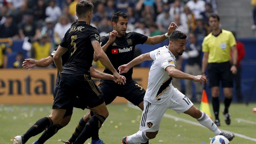 Galaxy midfielder Sebastian Lletget, right, attracts three LAFC defenders during a March 31 game at StubHub Center in Carson. The Galaxy came from behind to win 4-3.