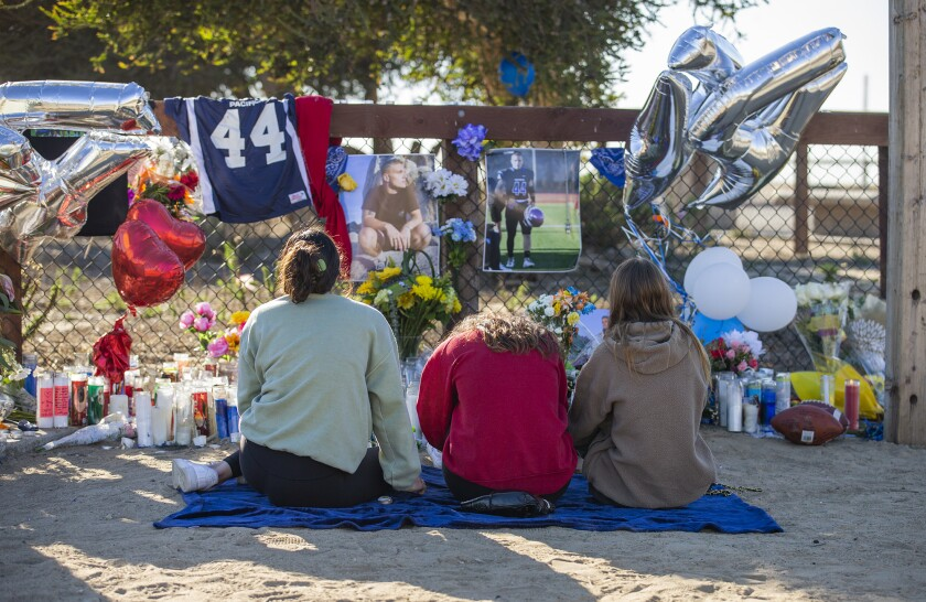 Teens sit by a roadside vigil for 19-year-old Mitch Wade in Sunset Beach on Thursday, Jan. 21.