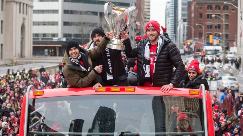 Toronto FC players Sebastian Giovinco (left to right), Victor Vazquez and Michael Bradley hold the MLS Cup trophy during a victory parade through downtown Toronto last month.