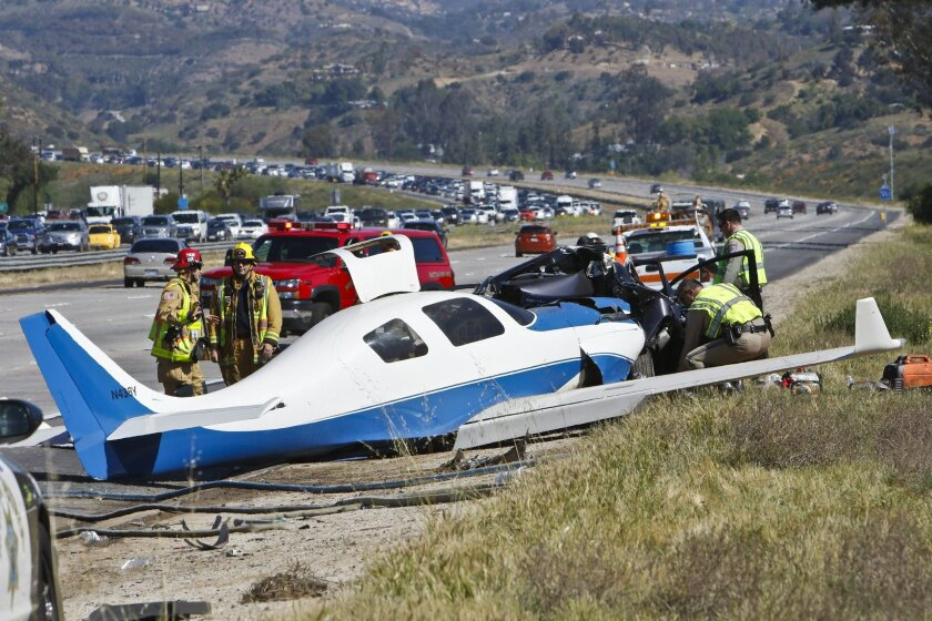 Emergency personnel investigate the scene of plane crash, Saturday, April 2, 2016 in Fallbrook, Calif. A small plane crashed on a Southern California freeway Saturday and struck a car, killing one person and injuring five others, authorities said. (Don Boomer/The San Diego Union-Tribune via AP)  NO