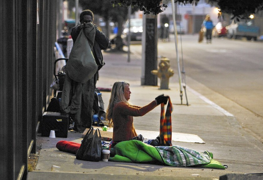 A woman awakened by LAPD officers on a sidewalk in Venice picks up her belongings.