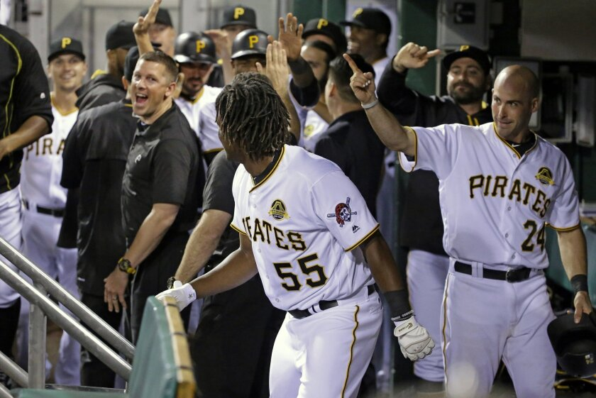 Teammates urge Pittsburgh Pirates' Josh Bell (55) to take a curtain call after he hit a grand slam off Chicago Cubs relief pitcher Adam Warren in the fifth inning of a baseball game in Pittsburgh, Saturday, July 9, 2016. (AP Photo/Gene J. Puskar)