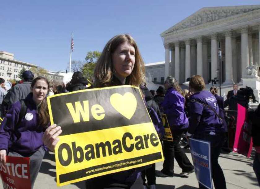 Supporters of President Obama's healthcare overhaul rally in front of the Supreme Court as the justices hear oral arguments on the 2010 reform law.