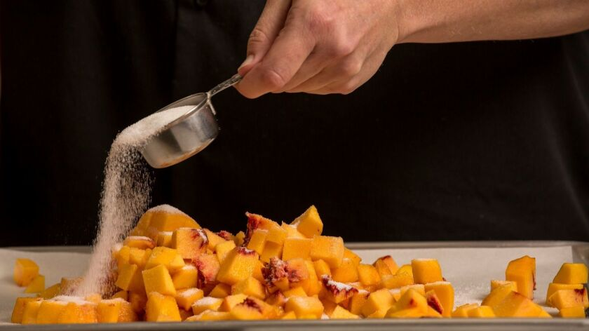 Diced peaches are coated with sugar for a frozen yogurt recipe being tried out in the Los Angeles Times test kitchen in 2016.