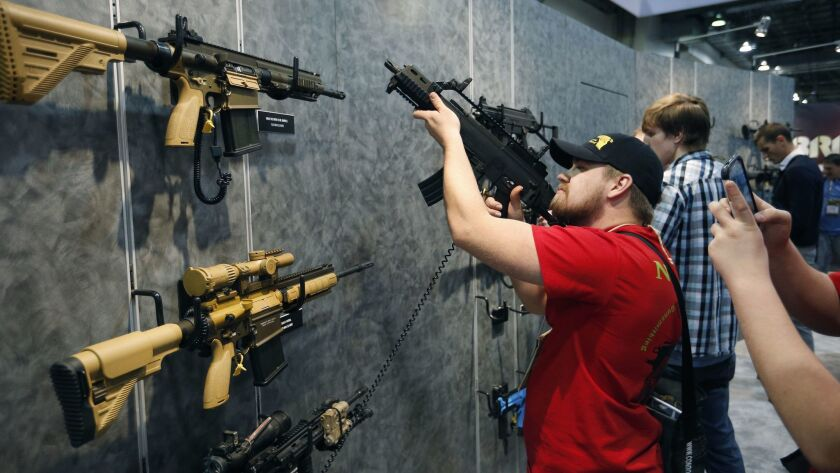 Nolan Hammer looks at a gun at the Heckler & Koch booth at the Shooting, Hunting and Outdoor Trade S