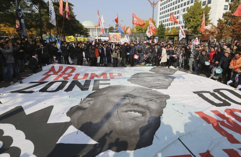Protesters hurl salt at a banner showing images of President Trump during a rally against his visit in front of the National Assembly in Seoul in November 2017.