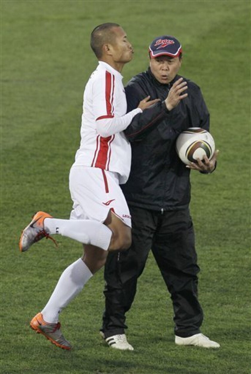 North Korea's Jong Tae Se, left, and head coach Kim Jong Hun practice during a team training session in Tembisa, South Africa, Friday June 11, 2010. North Korea are preparing for the upcoming soccer World Cup, where they will play in Group G.  (AP/Kin Cheung)