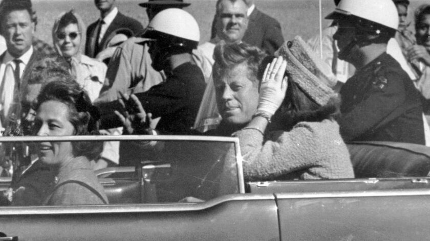 President John F. Kennedy waves from his car in a motorcade in Dallas, Texas on Nov. 22, 1963, the day he was killed.