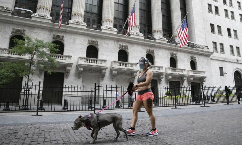 Una mujer con mascarilla pasea a su perro frente a la Bolsa de Valores de Nueva York, el martes 30 de junio de 2020, durante la pandemia de coronavirus. (AP Foto/Mark Lennihan)