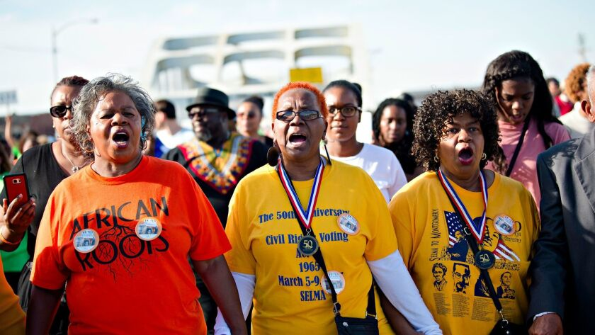 Marcia McMilan Edwards, left, Helen Brooks and Ruth Anthony lead the march across the Edmund Pettus Bridge on Sunday in Selma, Ala.