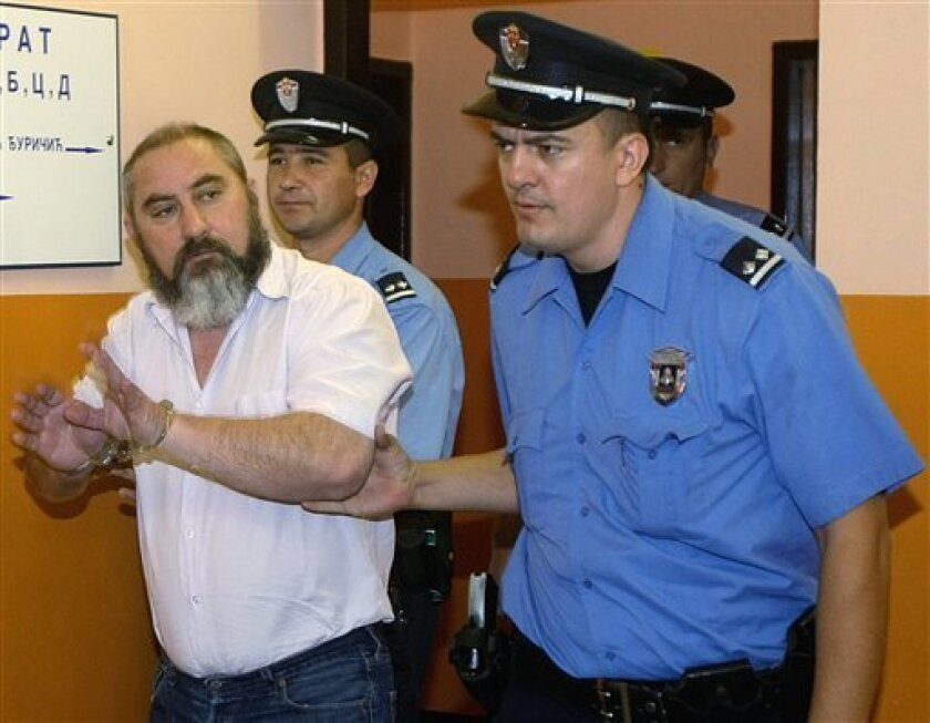 """Prison guards escort Damir Dokic to the courtroom for the retrial, Thursday, Sept. 24, 2009, in Ruma, northwest of Belgrade, Serbia. The father of tennis player Jelena Dokic, Damir Dokic was sentenced recently to 15-months in jail on charges that he """"endangering the security"""" of the Australian ambassador in Belgrade and unlawful possession of weapons, but a retrial was ordered after a higher court annulled the first verdict.(AP Photo/Srdjan Ilic)"""