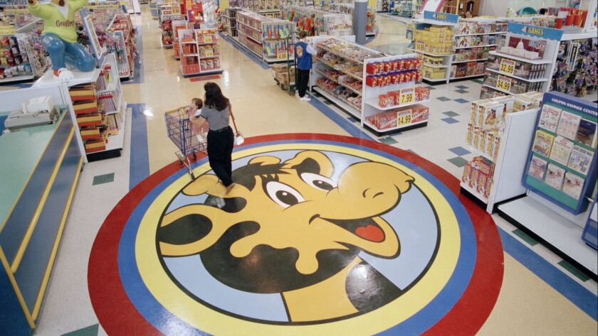 FILE- In this July 30, 1996, file photo, a woman pushes a shopping cart over a graphic of Toys R Us