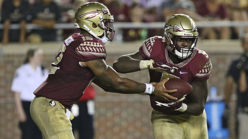 Florida State's Deondre Francois, left, hands the ball off to running back Jacques Patrick as they t