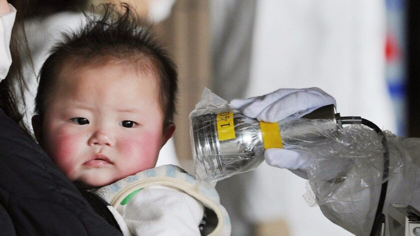 A baby is screened at an evacuation center for leaked radiation from the damaged Fukushima nuclear p