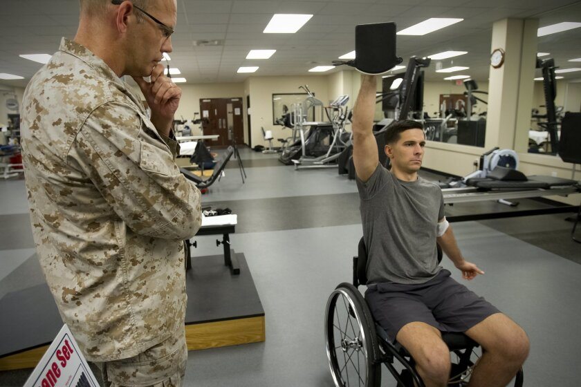Capt. Derek Herrera, of 1st Marine Special Operations Battalion, during physical therapy with Lt. Cmdr JD Garbrecht at Camp Pendleton. Herrera was paralyzed from the chest down when he was shot in June 2012 in southwestern Afghanistan.