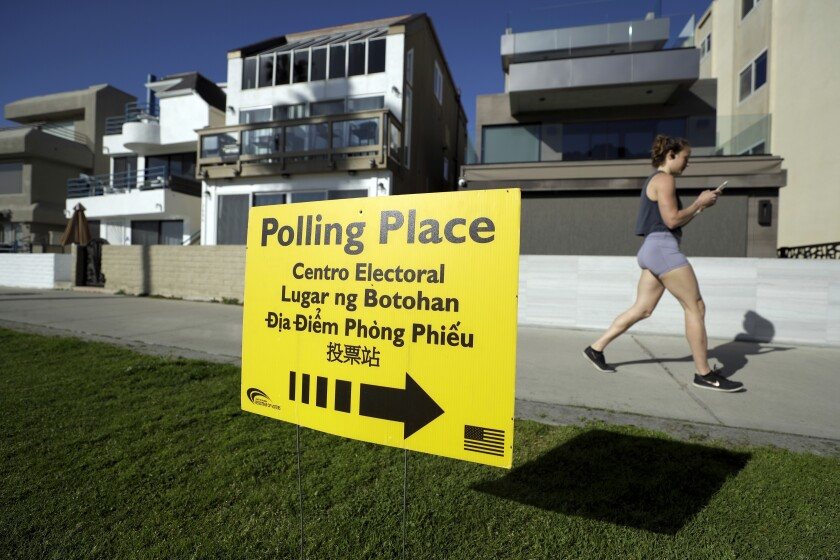 FILE - In this March 3, 2020 file photo, a woman runs on a path by a polling place during primary elections in San Diego. .On Thursday, Aug. 6, 2020, the California Legislature sent a bill to Gov. Gavin Newsom's desk that would let counties offer fewer in-person polling places if they keep them open at least four days. County election officials say they are having trouble securing enough polling places because of the pandemic. Senate bill 423 would let counties consolidate some polling places. (AP Photo/Gregory Bull, File)