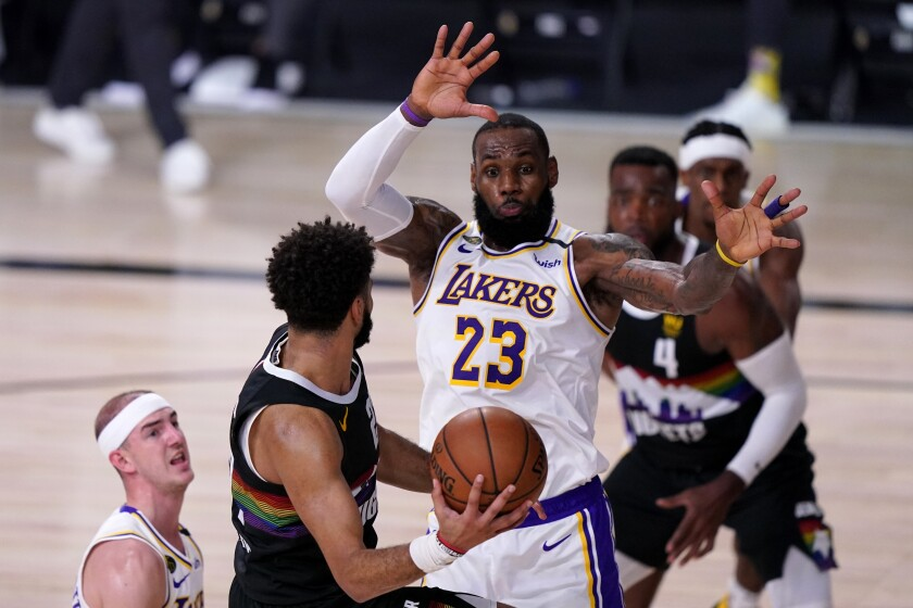 Lakers' LeBron James and Alex Caruso defend as Denver Nuggets guard Jamal Murray attempts to pass.