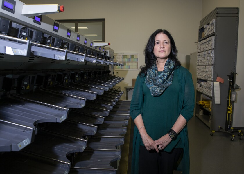 Cynthia L. Paes, San Diego County's interim Registrar of Voters, stands by a sorting machine