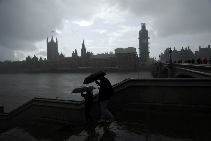 People are silhouetted with umbrellas in the rain backdropped by the Houses of Parliament in London, Tuesday, Sept. 24, 2019. In a major blow to Prime Minister Boris Johnson, Britain's highest court ruled Tuesday that his decision to suspend Parliament for five weeks in the crucial countdown to the country's Brexit deadline was illegal. (AP Photo/Matt Dunham)