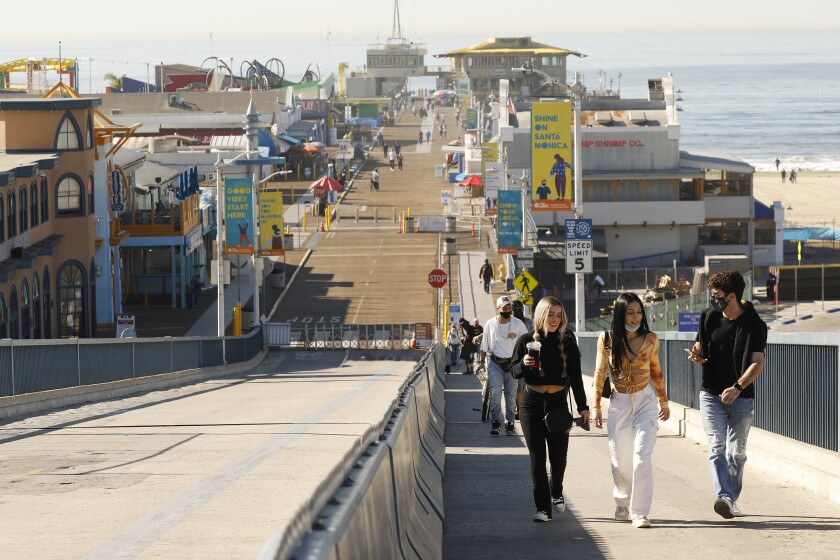 Young people walk near the beach and shops.
