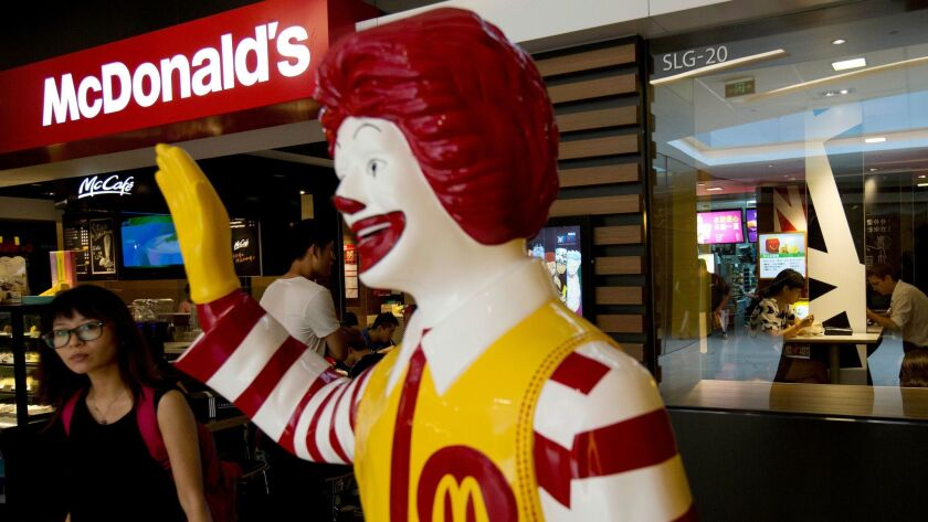 A customer walks past a statue of Ronald McDonald outside a McDonald's restaurant in Beijing in 2014.