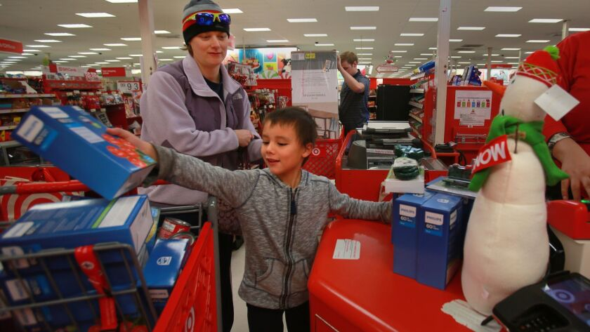Debbie Boezeman, with children Dainya, 5, (in the shopping basket), and Tanner, 7, Christmas shopping at Target in 2016.