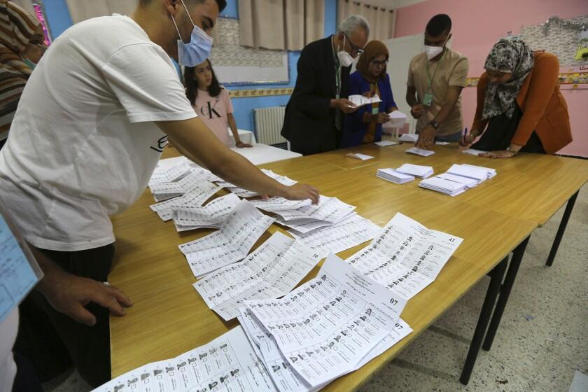 Funcionarios electorales cuentan boletas después del cierre de casillas en la primera elección legislativa de Argelia desde el derrocamiento del exmandatario Abdelaziz Bouteflika, el sábado 12 de junio de 2021, en Argel. (AP Foto/Anis Belghoul)