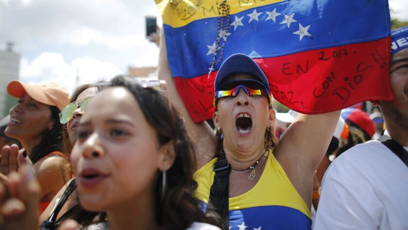 Anti-government protesters cheer during a rally demanding the resignation of Venezuelan President N