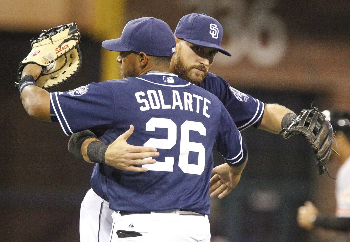 The Padres' Will Middlebrooks, right, and Yangervis Solarte hug as they celebrate the Padres 10-2 win over the Giants at Petco Park in San Diego on Saturday, April 11, 2015.