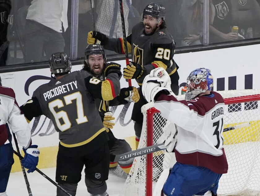 Vegas Golden Knights center Chandler Stephenson (20) and Vegas Golden Knights right wing Mark Stone (61) celebrate after Vegas Golden Knights left wing Max Pacioretty (67) scores a goal against Colorado Avalanche goaltender Philipp Grubauer (31) during the third period in Game 3 of an NHL hockey Stanley Cup second-round playoff series Friday, June 4, 2021, in Las Vegas. (AP Photo/John Locher)