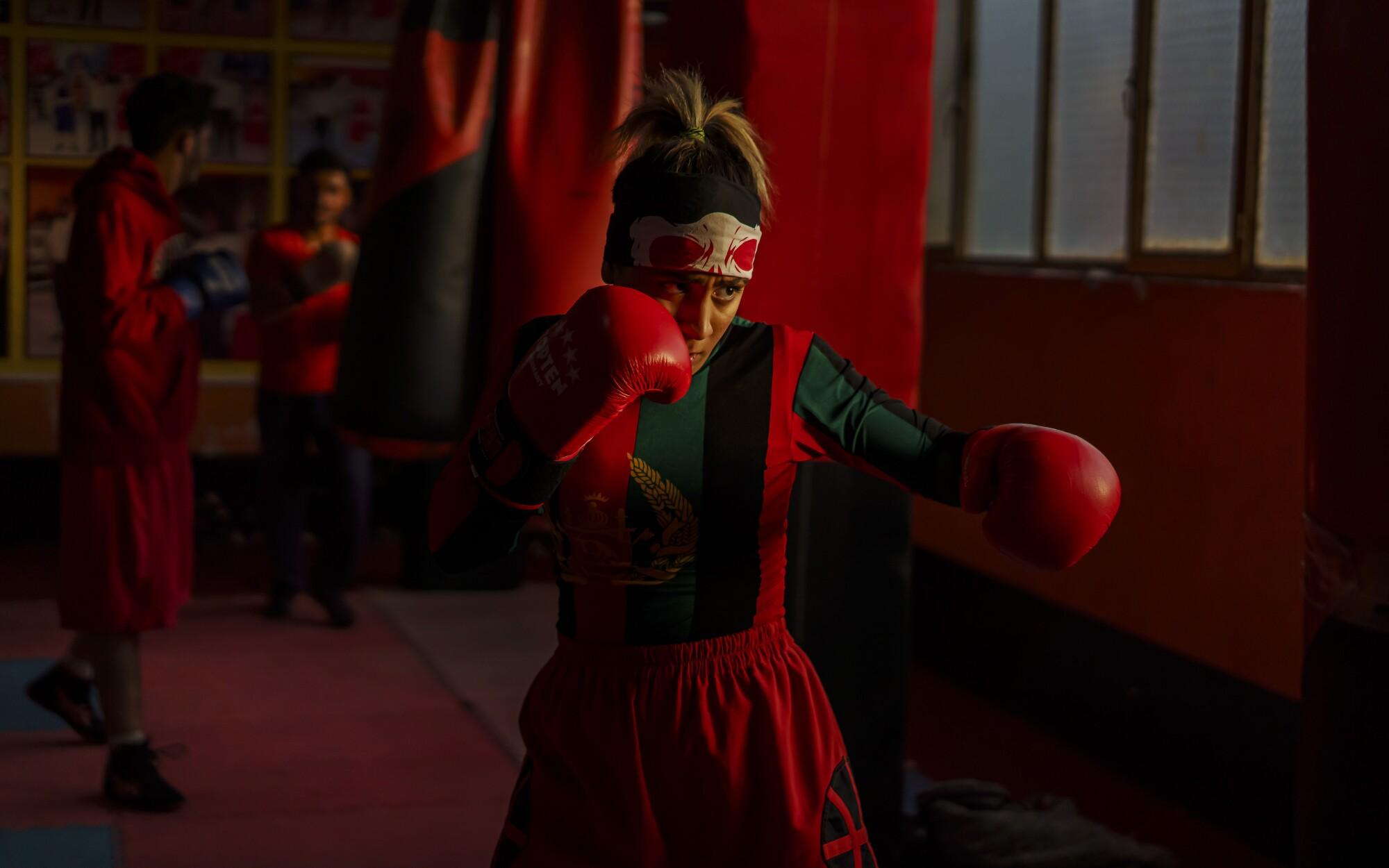 Khurshid Muhammadi, in boxing gloves, holds a fighting stance inside a Kabul gym.