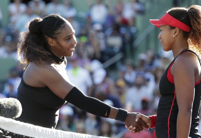 Naomi Osaka shakes hands with Serena Williams.