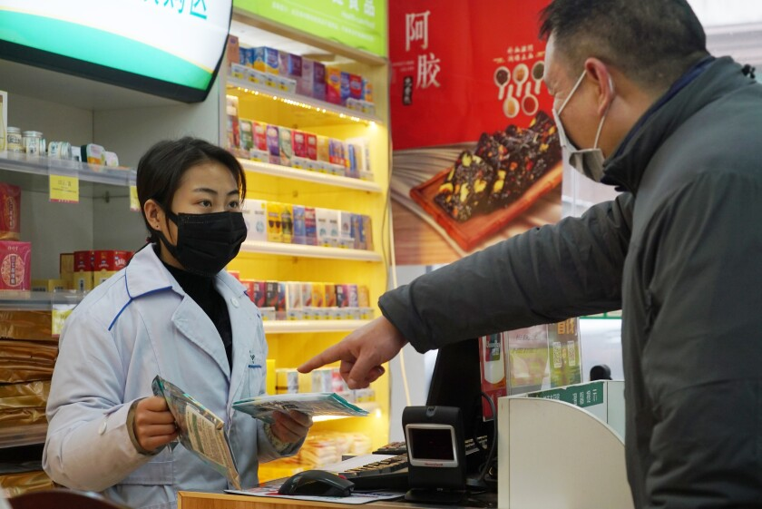 A man shops for face masks Jan. 22 at a pharmacy in Wuhan, China, where purchases were limited to one package per customer.