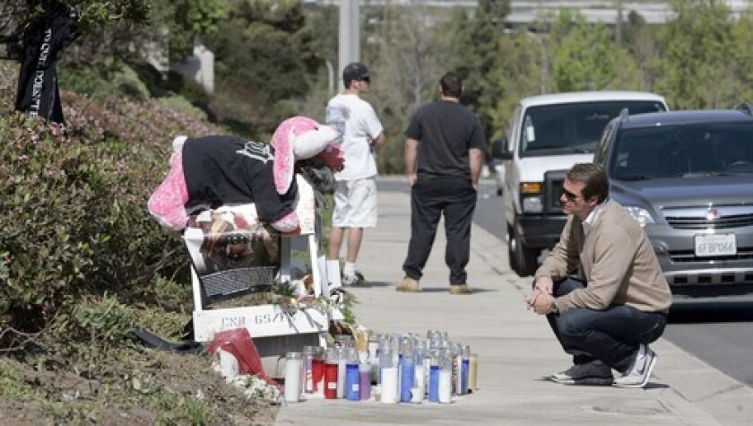 A man honors Charles Lewis at a roadside memorial. Lewis, a figure in the mixed martial arts scene, was killed when his Ferrari hit a light pole in Newport Beach.