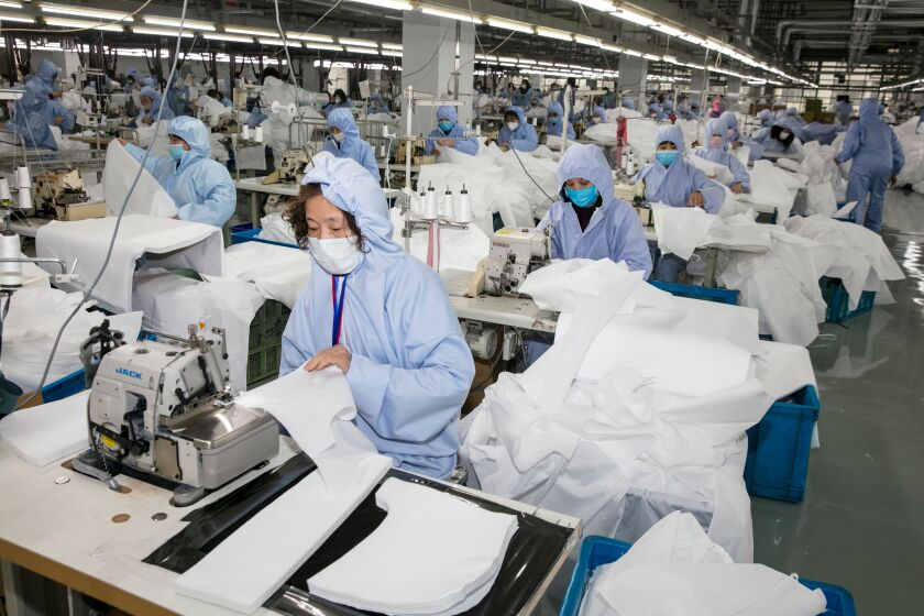 Workers make protective clothing to guard against the coronavirus at a factory in Wuxi, in China's eastern Jiangsu province, on Feb. 8.