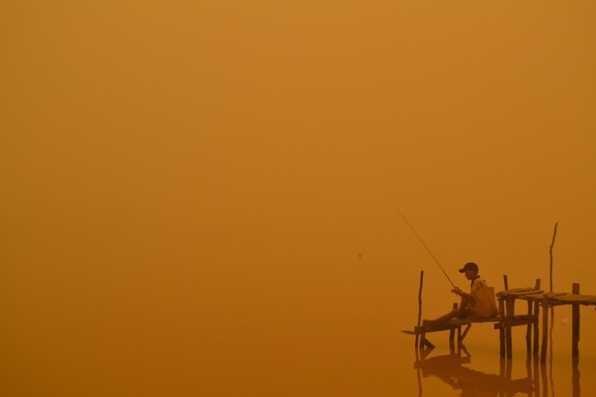 A resident fishes by the river in Palangkaraya, one of the cities worst-hit by haze in Indonesia's central Kalimantan province.