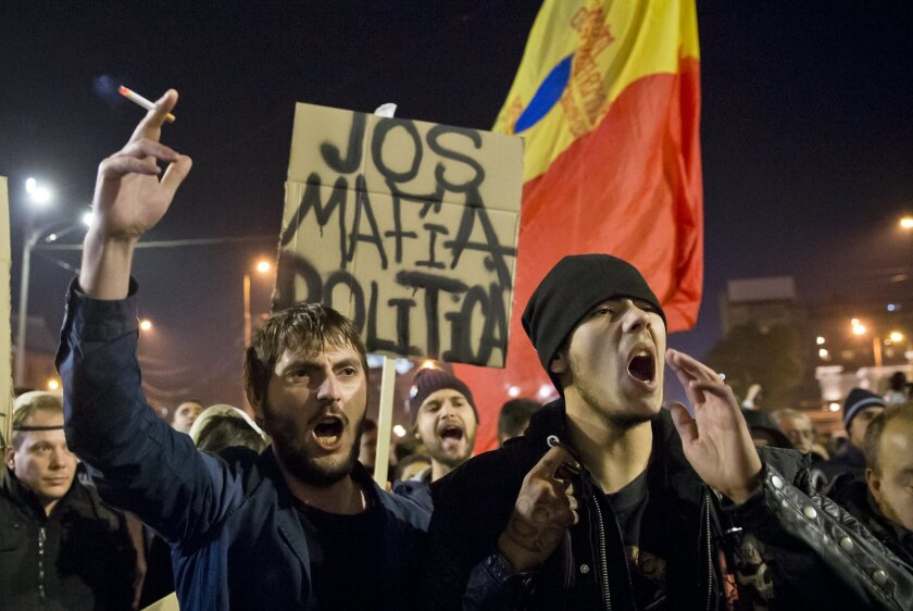 """Protesters shout slogans calling for early elections and hold banners that read: """"Down the Political Mafia"""" after a rally joined by thousands blocked traffic in University Square in Bucharest, Romania, Wednesday, Nov. 4, 2015. Prime Minister Victor Ponta announced the resignation of his government"""