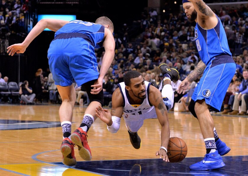 Memphis Grizzlies guard Mike Conley, center, falls to the court between Dallas Mavericks forward Chandler Parsons, left, and guard Deron Williams (8) in the second half of an NBA basketball game Saturday, Feb. 6, 2016, in Memphis, Tenn. (AP Photo/Brandon Dill)