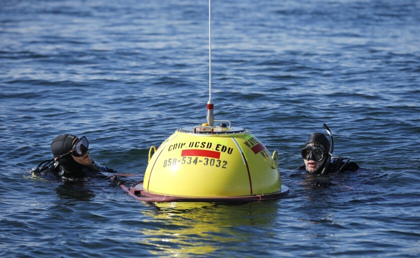 Les Hanson, left, and Jim Behrens of the Coastal Data Information Program make final adjustments on a wave buoy off the coast of Del Mar on Dec. 5, 2019. The buoy measures wave heights and current patterns near the area where bluffs have collapsed.