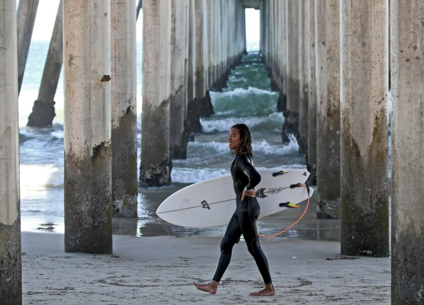 Kevin Tran walks under the pier after a day of surfing in Huntington Beach on July 31.
