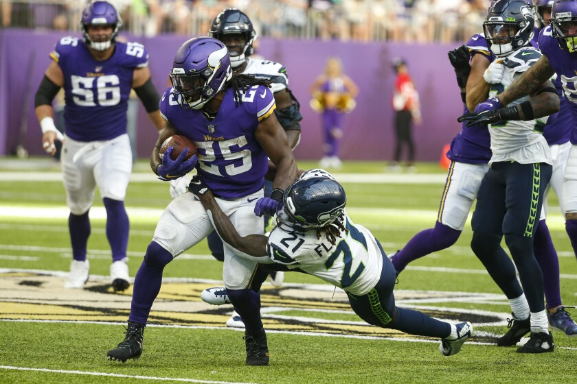 Minnesota Vikings running back Alexander Mattison (25) is tackled by Seattle Seahawks cornerback Tre Flowers (21) in the first half of an NFL football game in Minneapolis, Sunday, Sept. 26, 2021. (AP Photo/Bruce Kluckhohn)