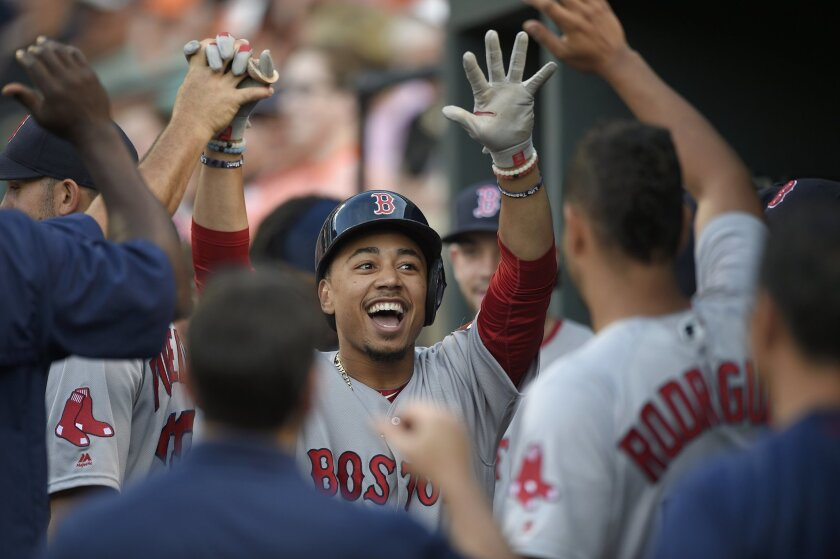 Boston Red Sox' Mookie Betts celebrates his home run in the dugout during the first inning of a baseball game against the Baltimore Orioles, Tuesday, May 31, 2016, in Baltimore. (AP Photo/Nick Wass)
