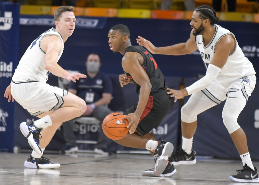 SDSU guard Lamont Butler dribbles the ball as Utah State forward Justin Bean (34) and forward Alphonso Anderson defend.