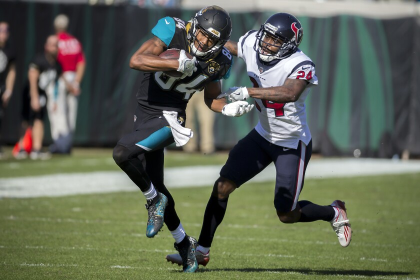FILE - In this Sunday, Dec. 17, 2017, file photo, Jacksonville Jaguars wide receiver Keelan Cole (84) is tackled by Houston Texans cornerback Johnathan Joseph (24) during the first half of an NFL football game in Jacksonville, Fla. Defensive backs AJ Bouye and Johnathan Joseph will to use the Jaguars-Texans game in London on Nov. 3, 2019 to raise awareness of the fight against cancer. Bouye and Joseph, who have both lost parents to cancer, will donate their tickets to a lucky fan in an effort to raise more awareness for the NFL's Crucial Catch's mission.(AP Photo/Stephen B. Morton, File)