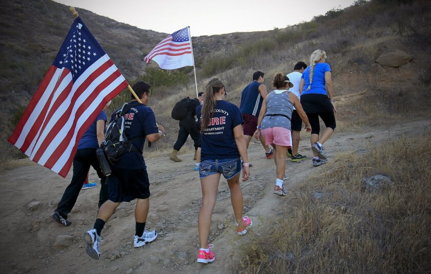 Rich Berry (foreground), an engineer paramedic with the North County Fire Protection District, carries an American flag as he and more than 200 people climbed to the top of Monserate Mountain during the Fallbrook Firefighters 9/11 Memorial Hill Climb Saturday.