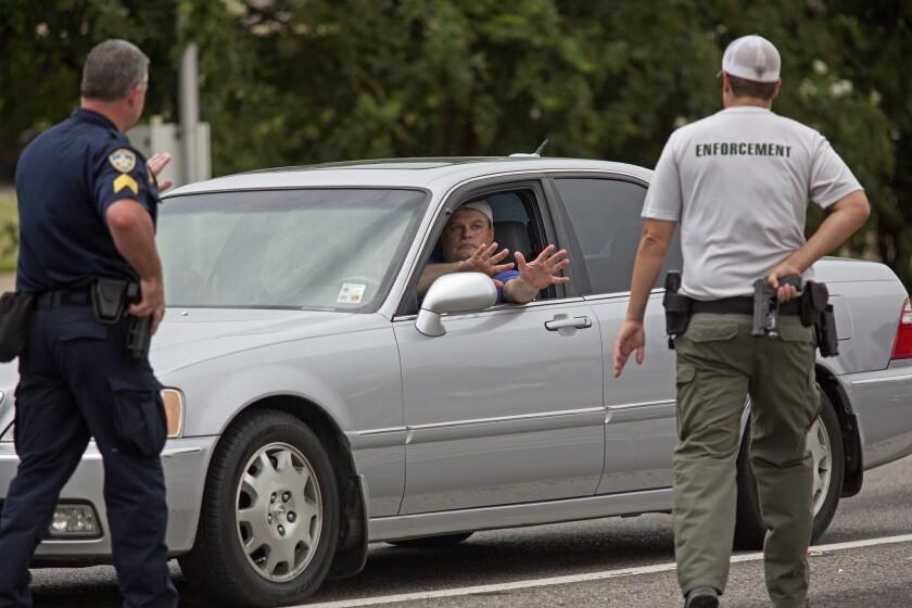 Policías detienen un vehículo y ordenan al conductor que muestre sus manos porque provenía de la dirección donde ocurrió un ataque contra agentes en la autopista Airline en Baton Rouge, Lousiana, el domingo 17 de julio de 2016. El vehículo fue registrado, la identificación del hombre verificada y se le permitió que continuara su camino. Varios agentes fueron muertos y otros heridos durante un ataque a tiros cerca de una gasolinera en Baton Rouge, menos de dos semanas después de que policías mataran a un hombre negro, hecho que desató protestas nocturnas en toda la ciudad. (AP Foto/Max Becherer)