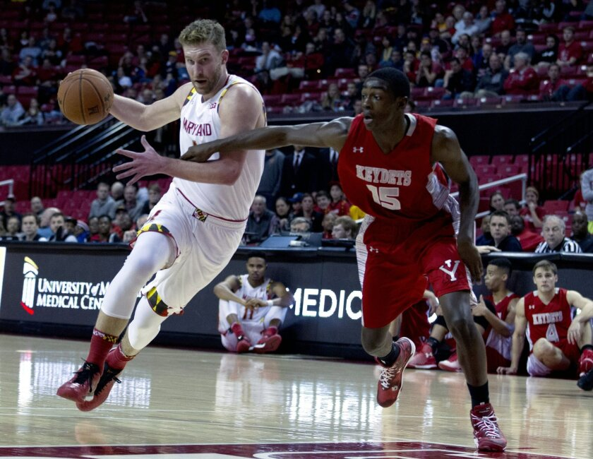 Maryland's Evan Smotrycz, left, drives the ball as VMI's Trey Chapman (15) tries to block during the first half of an NCAA college basketball game in College Park, Md., Sunday, Nov. 30, 2014. (AP Photo/Jose Luis Magana)