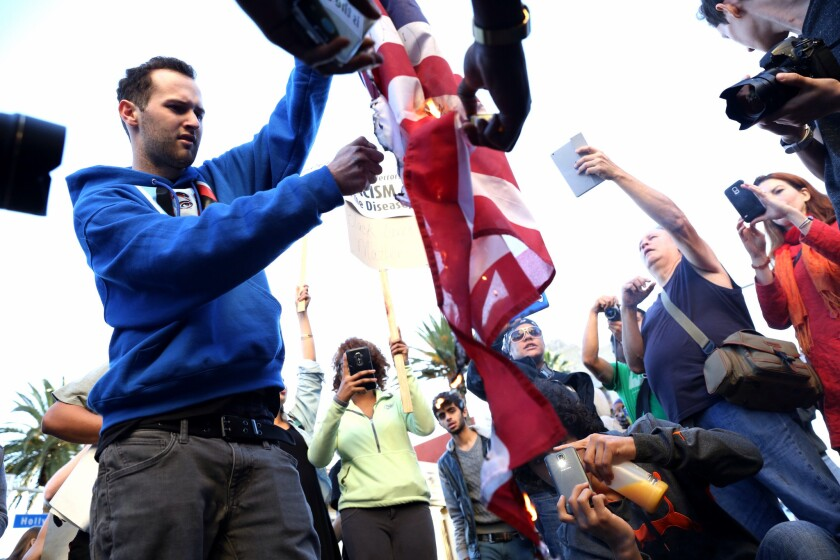 A protester burns an American flag during a 2014 rally against police violence in Los Angeles