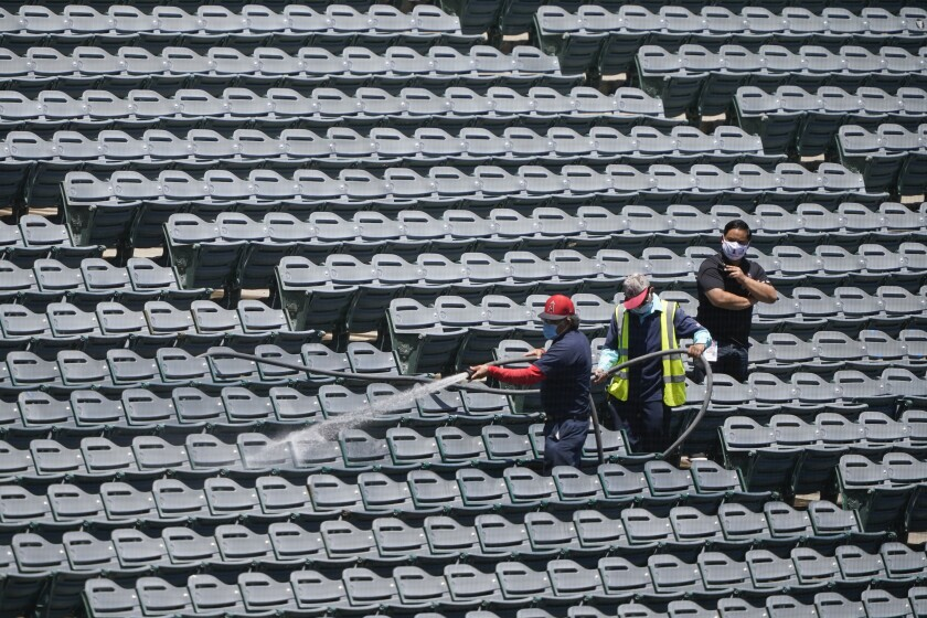 """File-Crews hose down stadium seats before the Los Angeles Angels baseball team practiced at Angel Stadium on Tuesday, July 7, 2020, in Anaheim, Calif. Every year in August, tens of thousands of people fill the seats of Angel Stadium in Anaheim, not for baseball, but for the weekend-long Harvest Crusade. his year, amid a global pandemic, Harvest Crusade will be different. Instead of the in-person stadium event, Harvest ministries will stream a cinematic crusade titled """"A Rush of Hope,"""" a film that will be released on Labor Day weekend. (AP Photo/Ashley Landis, File)"""