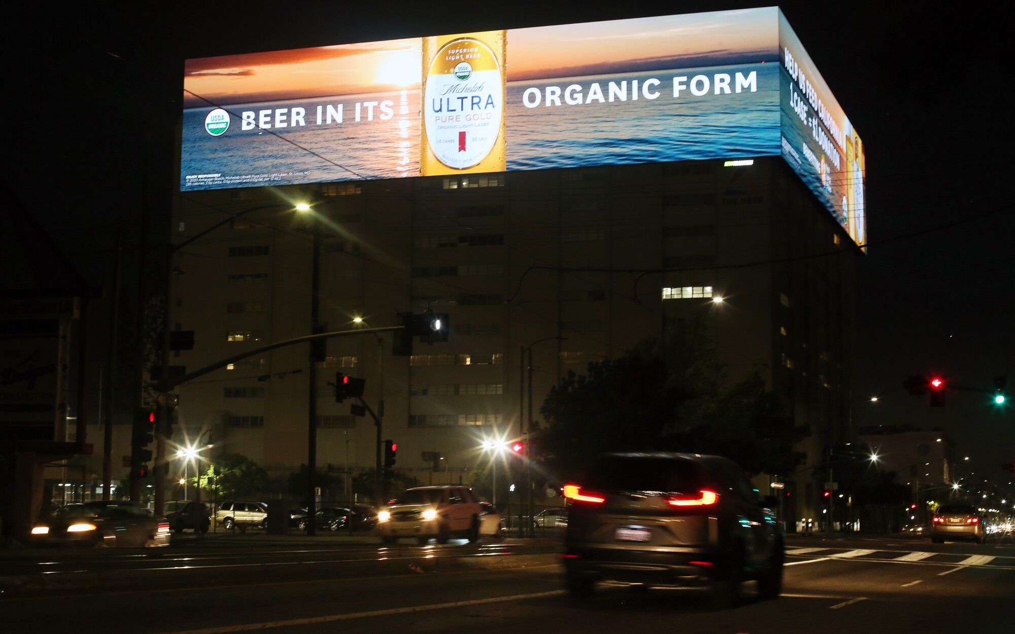 Cars on a nighttime city street pass below brightly lighted electronic billboards advertising beer